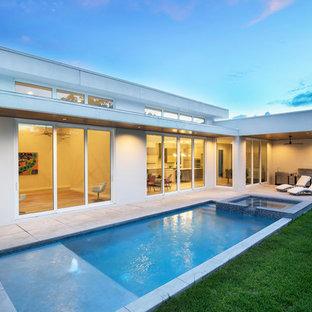 Immagine di una piccola piscina monocorsia minimal rettangolare dietro casa con una vasca idromassaggio e lastre di cemento