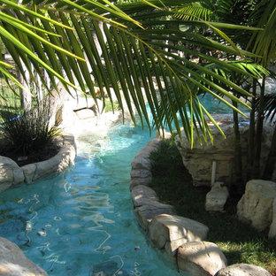 Idee per una grande piscina tropicale personalizzata dietro casa con fontane