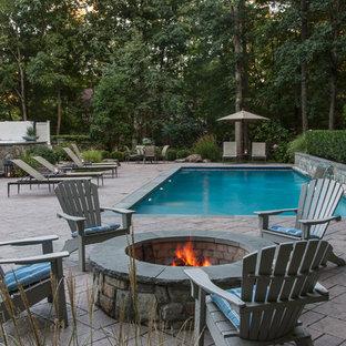 Ejemplo de piscina con fuente alargada, bohemia, de tamaño medio, rectangular, en patio trasero, con adoquines de hormigón
