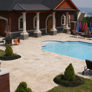 Example of a large mountain style courtyard stone and rectangular lap pool design in Tampa