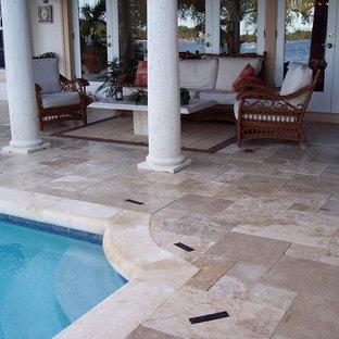 Diseño de piscina alargada, tradicional, de tamaño medio, en patio trasero, con adoquines de piedra natural