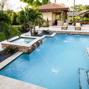 Ejemplo de piscinas y jacuzzis naturales, contemporáneos, de tamaño medio, rectangulares, en patio trasero, con adoquines de piedra natural