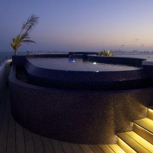Foto di una piscina a sfioro infinito design personalizzata sul tetto con una vasca idromassaggio e pedane