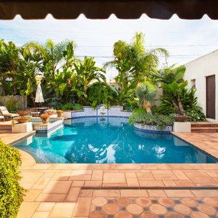 Modelo de piscinas y jacuzzis alargados, mediterráneos, de tamaño medio, rectangulares, en patio trasero, con adoquines de hormigón