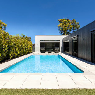 Inspiration for a large modern backyard pool in Melbourne with with privacy feature and concrete pavers.