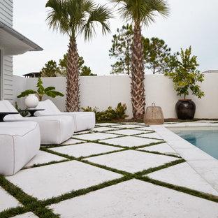 Foto de piscina alargada, actual, de tamaño medio, rectangular, en patio trasero, con adoquines de hormigón