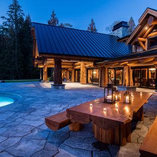 Modelo de piscinas y jacuzzis elevados, rústicos, extra grandes, tipo riñón, en patio trasero, con adoquines de hormigón