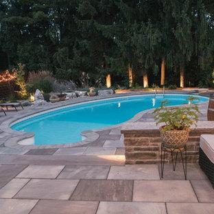 Esempio di una piscina monocorsia minimal rotonda di medie dimensioni e dietro casa con pavimentazioni in pietra naturale e una dépendance a bordo piscina