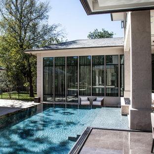 Imagen de piscina infinita, moderna, grande, en forma de L, en patio trasero, con adoquines de piedra natural