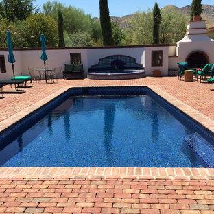 Ejemplo de piscinas y jacuzzis alargados, de estilo americano, grandes, rectangulares, en patio trasero, con adoquines de ladrillo