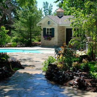 """Foto di una piscina monocorsia tradizionale a """"C"""" dietro casa e di medie dimensioni con una dépendance a bordo piscina e pavimentazioni in pietra naturale"""