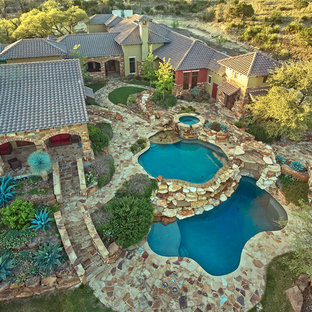 Inspiration for a large rustic backyard stone and custom-shaped hot tub remodel in Austin