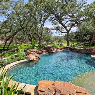 Esempio di una grande piscina naturale rustica personalizzata con pedane