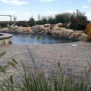 Diseño de piscinas y jacuzzis naturales, rústicos, grandes, a medida, en patio trasero, con suelo de hormigón estampado