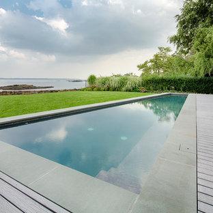 Idee per una grande piscina monocorsia minimal personalizzata dietro casa con pedane