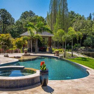 Modelo de piscinas y jacuzzis infinitos, clásicos, tipo riñón, en patio trasero, con adoquines de piedra natural