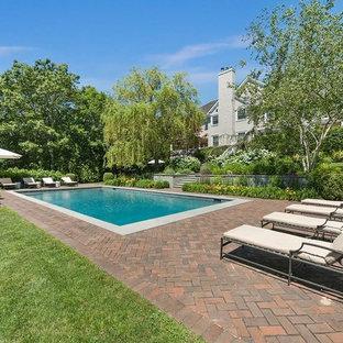 Foto de piscina costera, grande, rectangular, en patio trasero, con adoquines de ladrillo
