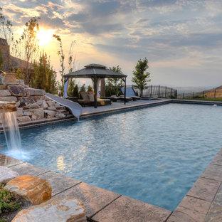 Imagen de piscina con tobogán alargada, rústica, rectangular, en patio trasero