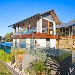 Ejemplo de casa de la piscina y piscina elevada, actual, grande, en forma de L, en patio trasero, con suelo de baldosas