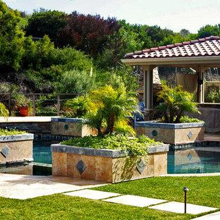 Ejemplo de casa de la piscina y piscina mediterránea, de tamaño medio, a medida, en patio trasero, con suelo de baldosas