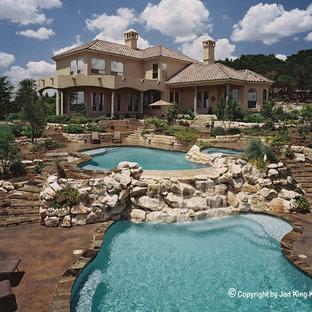 На фото: огромный естественный бассейн произвольной формы на заднем дворе в стиле рустика с домиком у бассейна и мощением тротуарной плиткой с