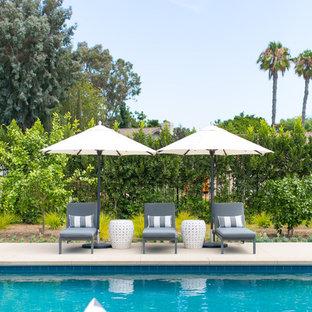 Foto de piscina alargada, clásica renovada, grande, rectangular, en patio trasero, con losas de hormigón