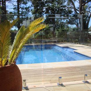 Cette photo montre une grand piscine sur une terrasse en bois hors-sol et arrière bord de mer rectangle avec un aménagement paysager autour d'une piscine.