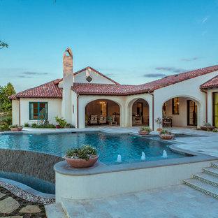 Diseño de piscina infinita, de estilo americano, extra grande, a medida, en patio trasero, con adoquines de piedra natural