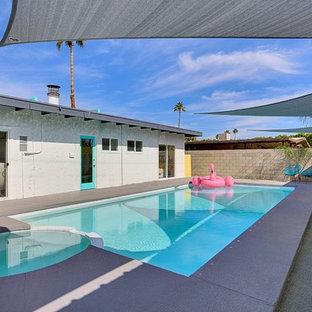 Modelo de piscinas y jacuzzis alargados, vintage, grandes, rectangulares, en patio trasero, con losas de hormigón