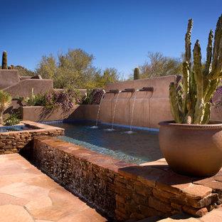 Ejemplo de piscinas y jacuzzis infinitos, de estilo americano, de tamaño medio, rectangulares, en patio trasero, con adoquines de piedra natural