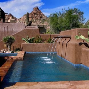 Diseño de piscinas y jacuzzis infinitos, de estilo americano, de tamaño medio, rectangulares, en patio trasero, con adoquines de piedra natural