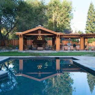 Cette image montre un très grand couloir de nage arrière craftsman sur mesure avec des pavés en pierre naturelle et un bain bouillonnant.