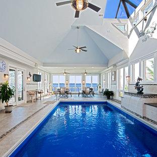 Esempio di una grande piscina coperta monocorsia tradizionale rettangolare con piastrelle e fontane