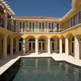 Example of a tuscan courtyard custom-shaped pool design in Miami
