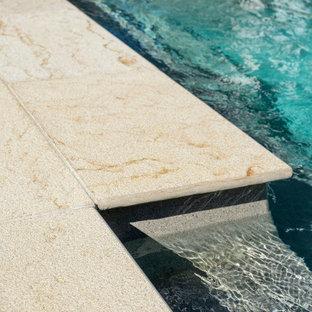 Ejemplo de piscina alargada, costera, de tamaño medio, rectangular, en patio trasero, con adoquines de piedra natural