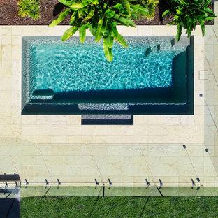 Modelo de piscina alargada, costera, de tamaño medio, rectangular, en patio trasero, con adoquines de piedra natural