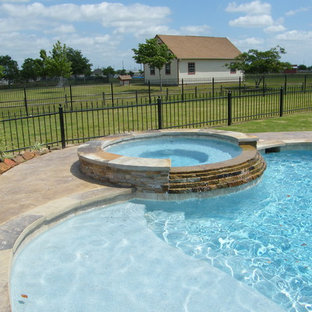 Large mountain style backyard stamped concrete and custom-shaped water slide photo in Houston