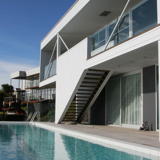 Diseño de piscina alargada, actual, rectangular, en patio delantero, con suelo de baldosas