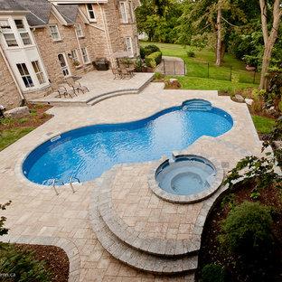 Ejemplo de piscinas y jacuzzis naturales, de estilo de casa de campo, de tamaño medio, tipo riñón, en patio trasero, con adoquines de piedra natural
