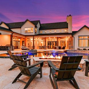 Foto de piscina natural, de estilo americano, grande, a medida, en patio trasero, con adoquines de piedra natural