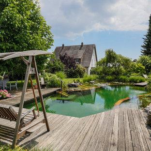 Modelo de piscina natural, de estilo de casa de campo, grande, a medida, en patio lateral, con entablado