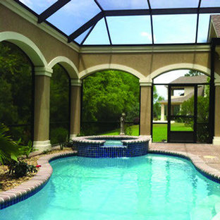 Exempel på en stor exotisk njurformad pool, med poolhus