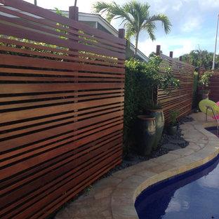 ハワイの中サイズのキドニーシェイプトロピカルスタイルのおしゃれなプール (天然石敷き) の写真