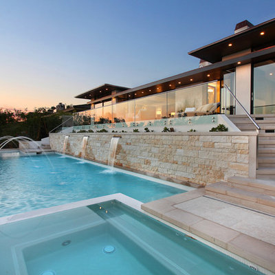 Inspiration for a mid-sized contemporary backyard stone and rectangular infinity hot tub remodel in Los Angeles
