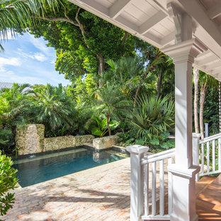 マイアミの中サイズの長方形トロピカルスタイルのおしゃれな横庭プール (レンガ敷き) の写真