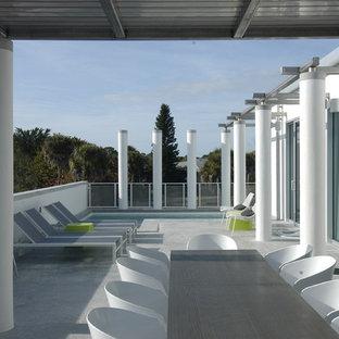 """Idee per una piccola piscina fuori terra minimal a """"L"""" in cortile con lastre di cemento"""
