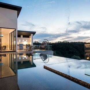 Ispirazione per una piscina a sfioro infinito moderna dietro casa con una vasca idromassaggio e pedane