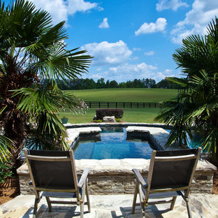 Elegant stone and custom-shaped pool photo in Atlanta