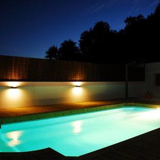Ejemplo de piscina con fuente marinera, de tamaño medio, rectangular, en azotea, con entablado