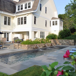Design ideas for an expansive arts and crafts side yard rectangular lap pool in DC Metro with a water feature and natural stone pavers.